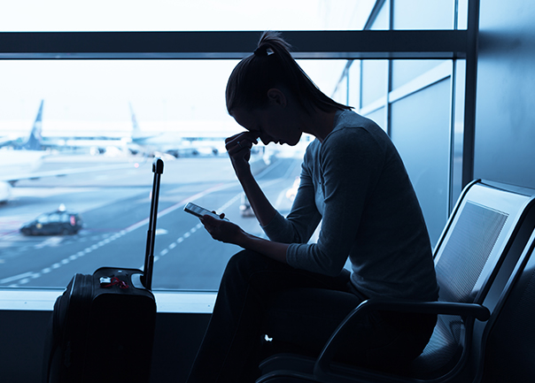 Image of nervous and looking at phone in airport