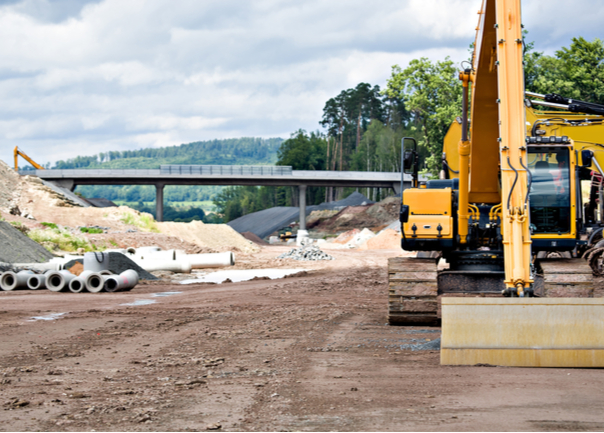 Road construction site with digger in foreground and bridge in background