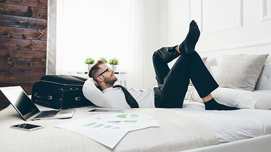 Male business traveller lying on hotel bed