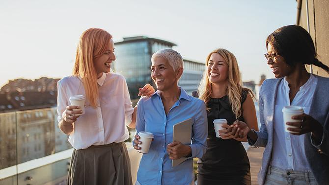CoT-HW-4 female professionals with coffee laughing together on balcony with buildings in the background