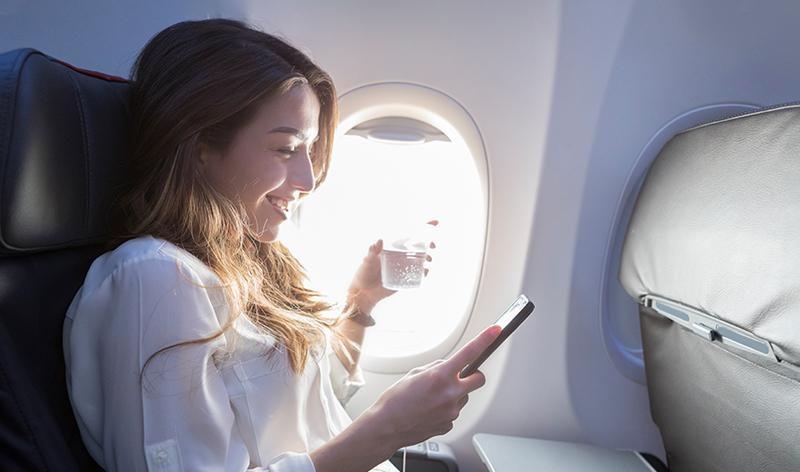Lady on plane looking at phone